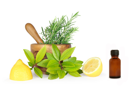 Fresh herb selection of rosemary, bay leaves and two lemon halves, with an olive wood pestle and mortar and an aromatherapy essential oil brown glass bottle. Set against a white background.